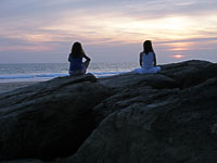 two figures watch sunset on rocks
